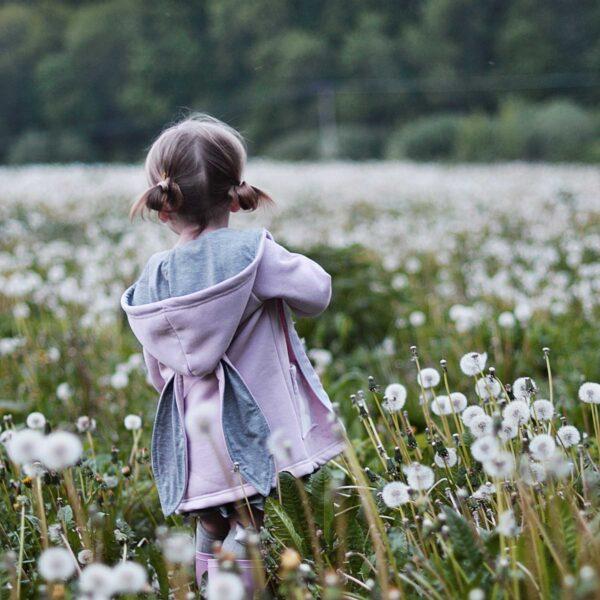 Dziewczynka na łące w płaszczyku z uszami królika