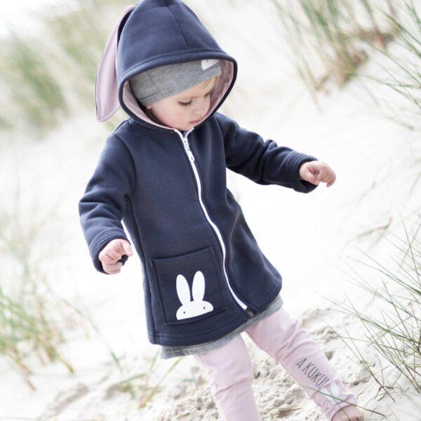 Dziewczynka w płaszczyku z uszami królika. Bluza z uszami królika