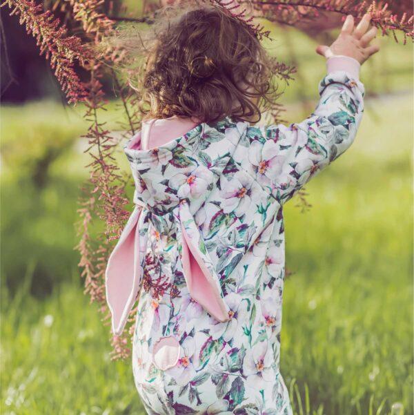 Dziewczynka w rampersie z uszami królika. Rampers zapinany na długi zamek.