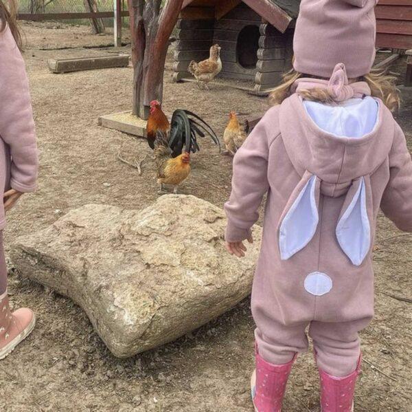 Dziewczynka w rampersie z uszami królika. Z tyłu naszyty płaski ogonek.