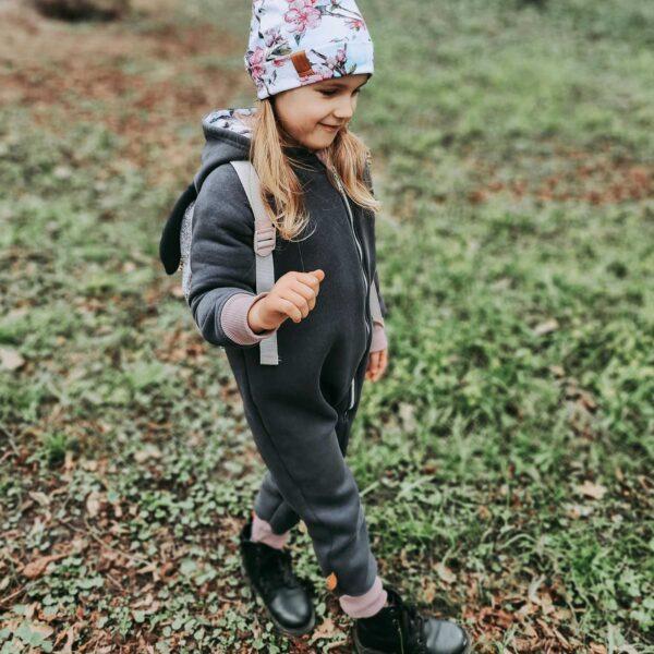 Dziewczynka w rampersie z uszami królika. Zapinany na długi zamek.