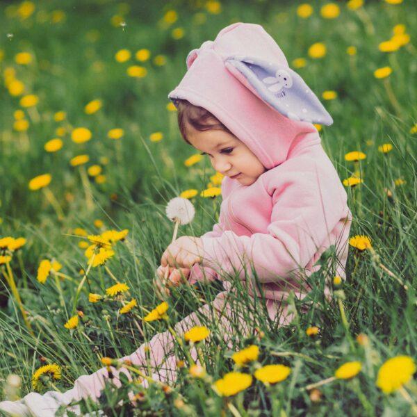 Dziewczynka w rampersie z uszami królika.