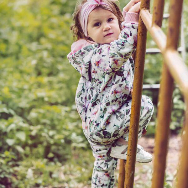 Dziewczynka w rampersie z uszami królika. Rampers w kwiatowy wzór. Zapinany na długi zamek.